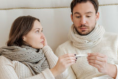 Shocked couple suffering from fever at home. Suffering from temperature. Ill young upset couple sitting on the bed at home and holding the thermometer while Stock Images