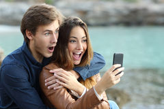 Shocked couple watching a smart phone on holidays Royalty Free Stock Photo