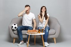 Shocked couple woman man football fans cheer up support favorite team covering eyes mouth with palms isolated on grey. Shocked couple women men football fans stock photography