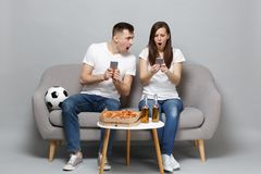 Shocked couple woman man football fans cheer up support favorite team, sitting holding using mobile phone isolated on. Shocked couple women men football fans royalty free stock image