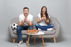 Shocked couple woman man football fans cheer up support favorite team with soccer ball, holding beer bottles  on stock photo