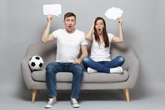 Shocked couple woman man football fans cheer up support favorite team with soccer ball holding empty blank Say cloud. Shocked couple women men football fans royalty free stock image