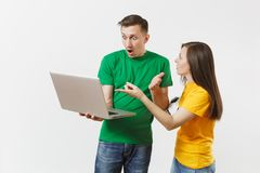 Shocked couple woman man, football fans in yellow green t-shirt cheer up support team with soccer ball, watching game on royalty free stock image