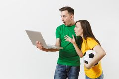 Shocked couple woman man, football fans in yellow green t-shirt cheer up support team with soccer ball, watching game on. Shocked couple women man, football fans royalty free stock photos
