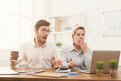 Couple of business partners work at modern office. Shocked couple of young business partners working in modern office. Two coworkers having trouble while working Stock Photography