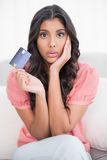Shocked cute brunette sitting on couch showing credit card Royalty Free Stock Images