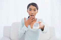 Shocked cute woman sitting on sofa changing tv channel Stock Photos