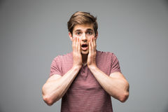 Shocked dazed young man holding head with both hands over grey background Royalty Free Stock Image