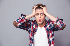 Shocked dazed young man holding head with both hands. Shocked dazed young man in plaid shirt holding head with both hands over grey background Stock Images
