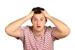 Shocked dazed young man in t-shirt holding head with both hands. emotional guy isolated on white background royalty free stock photography