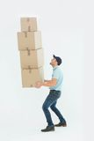 Shocked delivery man carrying stack of boxes