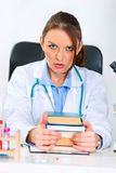 Shocked doctor woman sitting at table with books Stock Images