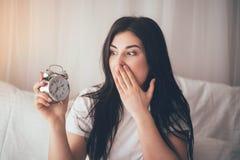 Shocked dorme demais mulher que acorda tarde fotografia de stock