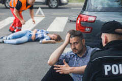 Shocked driver talking to policeman after car accident Stock Photos