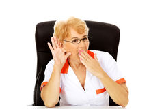 Shocked elderly female doctor or nurse sitting behind the desk and overhears a conversation Royalty Free Stock Photography