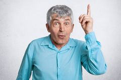 Shocked elederly handsome male has grey hair and wrinkled face, wears formal blue shirt, points with fore finger upwards, shows so stock images