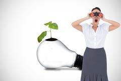 Shocked elegant businesswoman looking through binoculars Royalty Free Stock Photo
