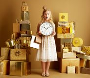 Shocked elegant girl with gold shopping bags and round clock royalty free stock image