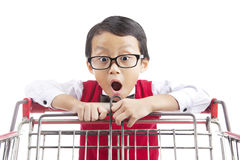 Shocked elementary school student. Face expression of shocked male elementary school student looking at shopping cart Royalty Free Stock Photography