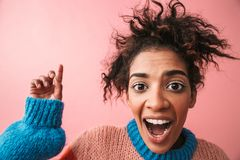 Shocked emotional beautiful young african woman posing isolated over pink wall background stock photography