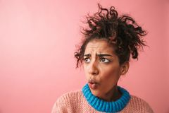 Shocked emotional beautiful young african woman posing isolated over pink wall background stock image