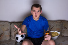 Shocked emotional supporter in uniform sitting on the sofa and w Stock Photos