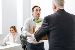 Shocked employee receiving the box with belongings from the employer. Shocking day of my life . Surprised puzzled perplexed employee standing and getting the box Stock Image