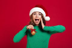 Shocked excited young lady wearing christmas santa hat royalty free stock images