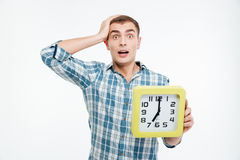 Shocked excited young man holding big clock Royalty Free Stock Photo