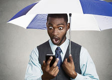 Shocked executive reading breaking news on a rainy day Royalty Free Stock Images