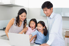 Shocked family of four using laptop in kitchen. Happy shocked family of four using laptop in the kitchen at home Stock Photos
