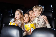 Shocked Family Watching Movie In Theater. Shocked family of four with popcorn watching movie in cinema theater Stock Photo