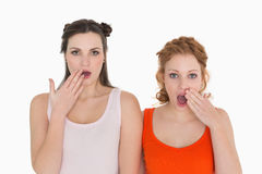 Shocked female friends with hand over mouth Stock Images