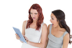 Shocked female friends looking at digital tablet Royalty Free Stock Photo