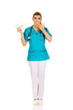 Shocked female nurse or doctor holding pills Royalty Free Stock Images
