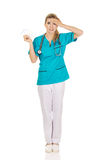 Shocked female nurse or doctor holding pills Royalty Free Stock Photo