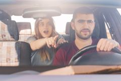 Shocked female sits on back seat in car, indicates at windscreen with terrified expression as sees awful accident on road and her. Bearded husband in foreground Royalty Free Stock Photo