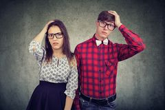Shocked forgetful couple man and woman holding hands on head royalty free stock images