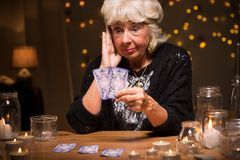 Shocked fortune teller reading cards Stock Photo