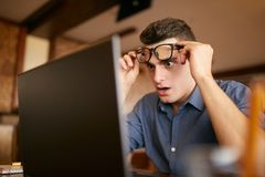 Shocked freelancer hipster man looks to laptop screen and can not believe unpleasant news. Pop-eyed frightened. Businessman trader raises one`s glasses above Stock Image