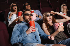 Shocked friends sitting in cinema watch film. Photo of shocked friends sitting in cinema watch film eating popcorn and drinking aerated sweet water royalty free stock photos