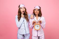 Shocked friends women in pajamas holding alarm clock. Image of two shocked friends women in pajamas isolated over pink background holding alarm clock. Looking ae royalty free stock photography