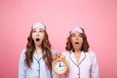 Shocked friends women in pajamas holding alarm clock. Image of two shocked friends women in pajamas isolated over pink background holding alarm clock. Looking ae stock photography