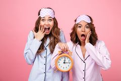 Shocked friends women in pajamas holding alarm clock. Picture of two shocked friends women in pajamas isolated over pink background holding alarm clock. Looking stock photo