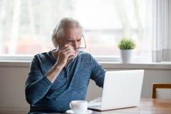 Shocked frustró al hombre mayor que sacaba los vidrios que miraban el lapt foto de archivo