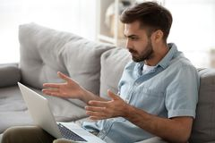 Shocked frustrated man looking at laptop screen, bad news receiving. Shocked frustrated man looking at laptop screen, reading bad news, receiving unpleasantly royalty free stock photo