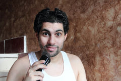 Shocked funny arab young man cutting hair with hair clipper Royalty Free Stock Image