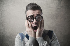 Shocked funny guy with head in hands. Shocked funny guy staring at camera with head in hands Royalty Free Stock Images