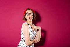 Shocked ginger woman in dress and eyeglasses looking at camera stock images