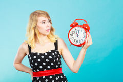 Shocked girl with alarm clock on blue. Stock Photos
